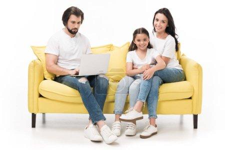 Foto de Centrado de hombre usando la laptop con la familia descansando en el sofá cerca de aislados en blanco - Imagen libre de derechos