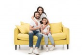 smiling woman hugging family on yellow sofa isolated on white