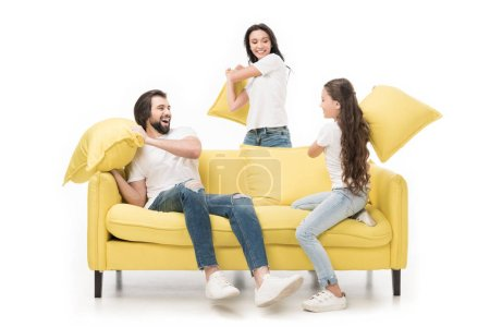 Photo for Happy family in white shirts on yellow sofa having pillow fight isolated on white - Royalty Free Image