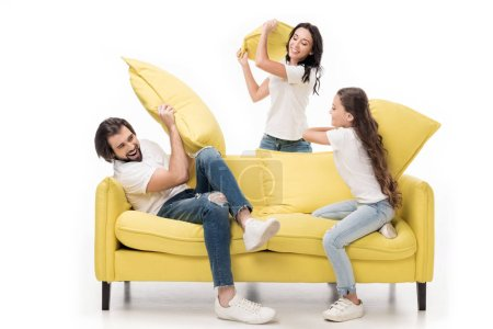 happy family in white shirts on yellow sofa having pillow fight isolated on white