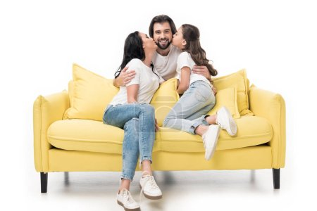 mother and daughter on yellow sofa kissing happy father isolated on white