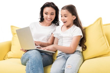 portrait of mother and happy daughter using laptop together on sofa isolated on white