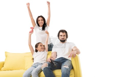 happy mother and daughter on yellow sofa playing video games with upset father near by isolated on white