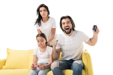 happy man and upset family playing video games on yellow sofa isolated on white