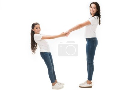 side view of happy mother and daughter in white shirts holding hands isolated on white