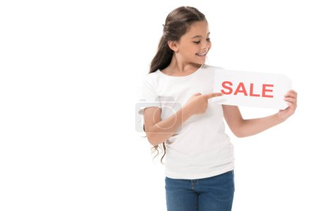 portrait of smiling kid pointing at sale banner in hand isolated on white