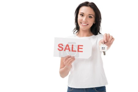 portrait of smiling woman with sale card showing keys isolated on white