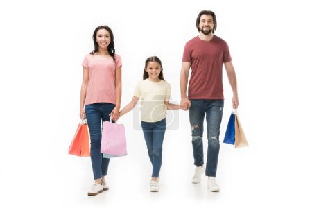 smiling family with shopping bags holding hands isolated on white
