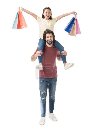 cheerful daughter with shopping bags sitting on fathers neck isolated on white