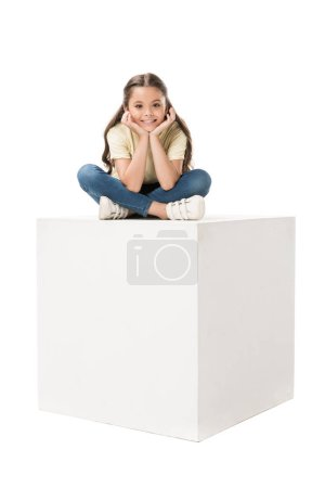 smiling child in casual clothing sitting on white cube isolated on white
