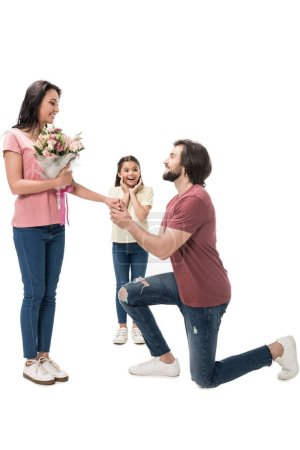 excited kid looking at smiling woman with bouquet of flowers and man standing on one knee isolated on white