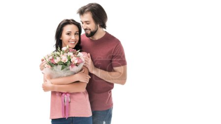 portrait of smiling woman with bouquet of flowers and husband isolated on white