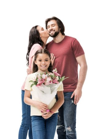 portrait of smiling daughter with bouquet of flowers with parents kissing behind isolated on white