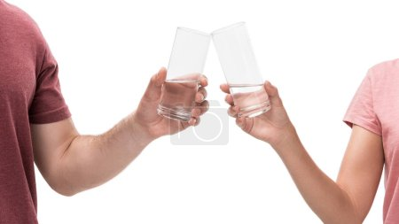 partial view of couple clinking glasses of water isolated on white