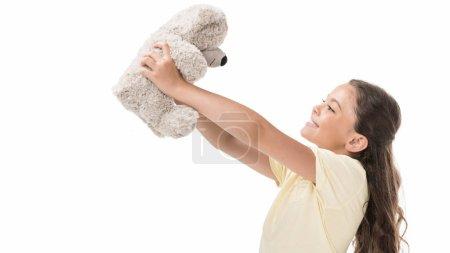 Foto de Vista lateral de lindo niño sonriente con oso de peluche aislado en blanco - Imagen libre de derechos