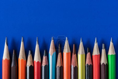 top view of colorful various pencils placed in row on blue background