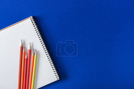 top view of various colorful pencils and blank textbook on blue background