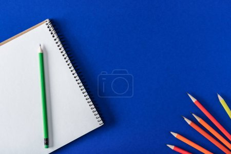 Photo for Top view of arranged variety pencils and blank textbook on blue background - Royalty Free Image