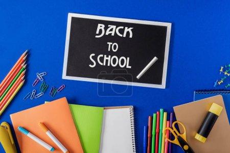 Photo pour Vue du dessus du tableau noir avec lettrage retour à l'école et papeterie de variété sur fond bleu - image libre de droit