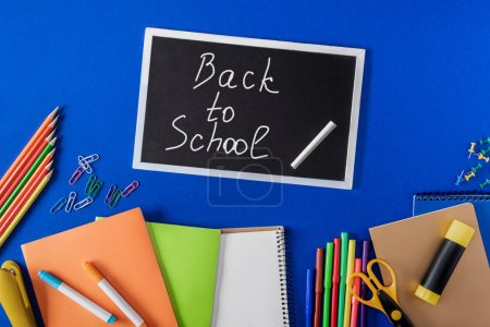 top view of chalkboard with lettering back to school and variety stationery on blue background