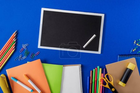 top view of blank blackboard with chalk and variety stationery on blue background