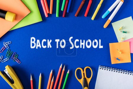 top view of lettering back to school from white paper surrounded by variety stationery on blue background