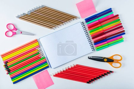 top view of blank notebook surrounded by colorful felt pens, pencils and scissors on white background