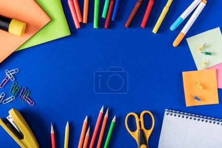 top view of colorful markers and pencils, empty textbook and variety stationery on blue background
