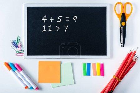 Photo pour Vue de dessus sur tableau noir avec des sommes de math et l'école de variété de fournitures de bureau sur fond blanc - image libre de droit