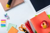 top view of apple, empty chalkboard and variety school supplies on white background