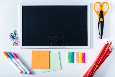 top view of empty chalkboard and variety school supplies on white background