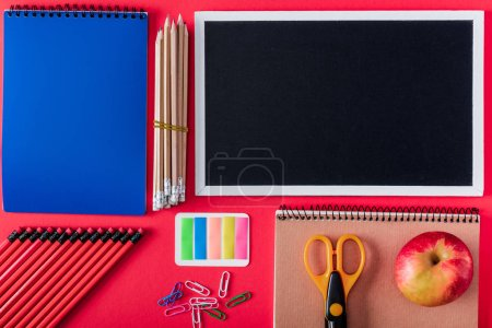 top view of blank blackboard, apple and arranged variety stationery on red background