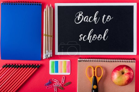 Photo for Top view of blackboard with lettering back to school, apple and arranged variety stationery on red background - Royalty Free Image