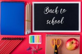 top view of blackboard with lettering back to school, apple and arranged variety stationery on red background