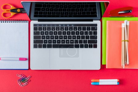 top view of laptop with blank screen and variety stationery on red background