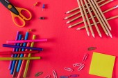 top view of colorful markers, scissors, pushpins, paper clips, stick it and pencils on red background