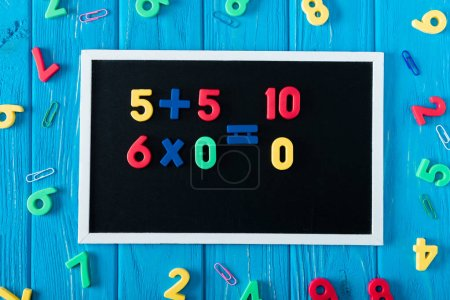 Photo for Top view of blackboard with math sums, colorful numbers and paper clips on blue wooden background - Royalty Free Image