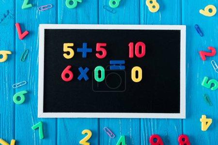 Photo pour Vue de dessus de tableau noir avec des sommes de math, numéros colorés et trombones sur fond en bois bleu - image libre de droit
