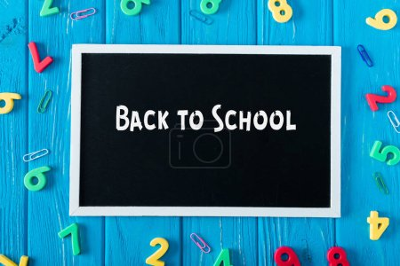 top view of blackboard with lettering back to school, paper clips and colorful numbers on blue wooden background