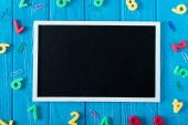 top view of empty blackboard, colorful numbers and paper clips on blue wooden background
