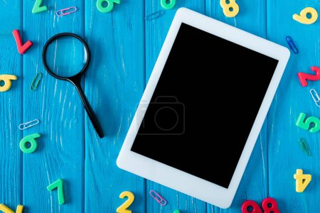 Photo for Top view of magnifier, digital tablet with blank screen, paper clips and numbers on blue wooden background - Royalty Free Image