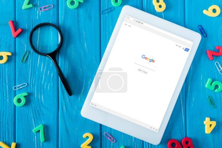 Photo for Top view of digital tablet with google website on screen, magnifier, paper clips and colorful numbers on blue wooden background - Royalty Free Image