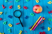 top view of magnifier, apple, colorful markers and various numbers on blue wooden background