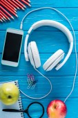 top view of headphones, smartphone with blank screen, apples and stationery on blue wooden background