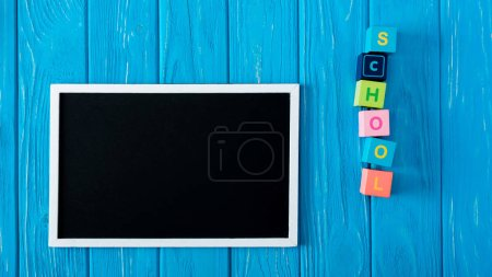 top view of blank blackboard and lettering school made from cubes on blue wooden background