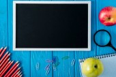 top view of blank chalkboard and empty textbook, apple, magnifier, pencils and paper clips on blue wooden background