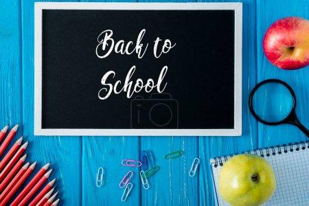 Foto de Vista superior de la pizarra con letras de nuevo a la escuela, las manzanas, cuaderno en blanco, lápices y clips de papel sobre fondo de madera azul - Imagen libre de derechos