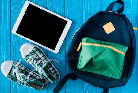 top view of digital tablet with blank screen, sneakers and rucksack on blue wooden background