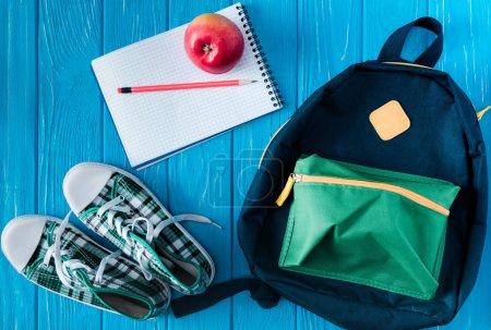 Foto de Vista superior de zapatillas de deporte, mochila, cuaderno vacío, manzana y lápiz sobre fondo de madera azul - Imagen libre de derechos