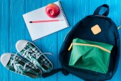 top view of sneakers, rucksack, empty notebook, apple and pencil on blue wooden background